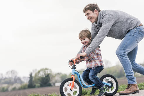 Father teaching his son how to ride a bicycle, outdoors - UUF17992