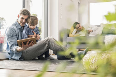 Father and son lying on floor, using digital tablet - UUF18022