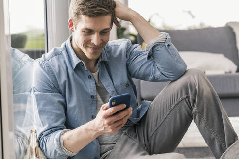Mid adult man sitting by window, using smartphone - UUF18025