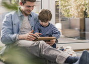 Father and son sitting on floor, using digital tablet - UUF18028