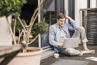 Man sitting on terrace, using laptop - UUF18037