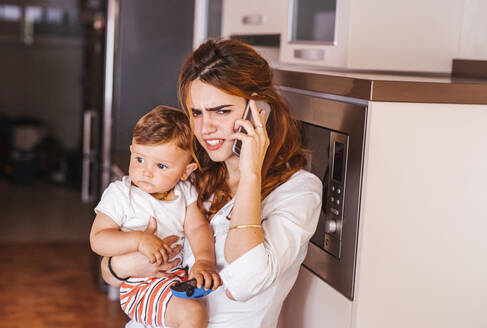 Annoyed mother with her son talking on the phone at home - LJF00266