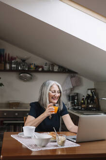 Portrait of laughing senior woman using laptop at breakfast table - ALBF00894