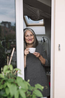 Portrait of happy senior woman leaning at opened balcony door with sup of coffee looking at distance - ALBF00897