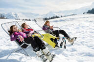 Three teenage girl skiers sitting in deck chairs in snow covered landscape, Tyrol, Styria, Austria - CUF51643