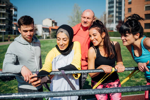 Calisthenics class at outdoor gym, men and women taking smartphone selfie - CUF51682