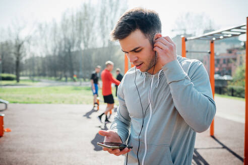 Calisthenics class at outdoor gym, young man putting in earphones - CUF51706
