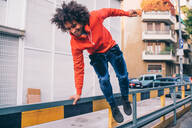 Young man jumping over divider on pavement, Milano, Lombardia, Italy - CUF51838