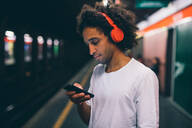 Young man using smartphone on train platform - CUF51841