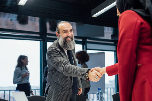 Business partners shaking hands at meeting in office - CUF51844