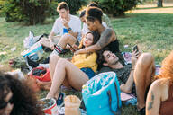 Group of friends relaxing at picnic in park - CUF51895