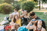 Group of friends relaxing, blowing bubbles at picnic in park - CUF51898