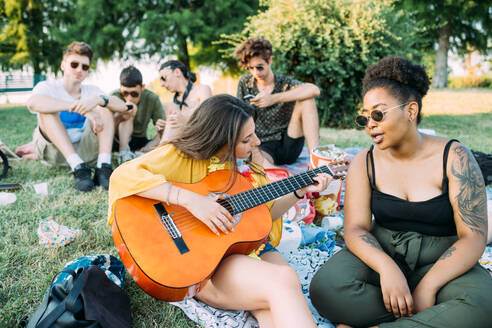 Group of friends relaxing, playing guitar at picnic in park - CUF51901