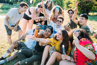 Group of friends taking selfie, playing with confetti in park - CUF51913