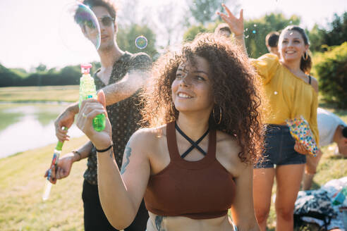 Group of friends playing with bubble gun in park - CUF51922