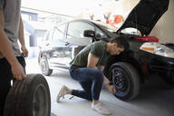 Teenage boy changing car tire in garage - HEROF36832
