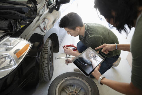 Mother and son with digital tablet learning to change car tire - HEROF36844