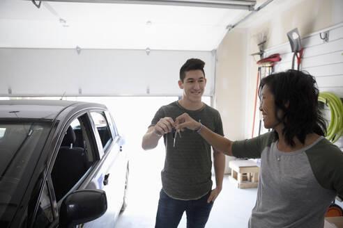 Mother handing car keys to teenage son in garage - HEROF36847