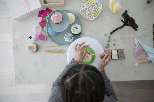 View from above teenage girl decorating cupcakes - HEROF36886