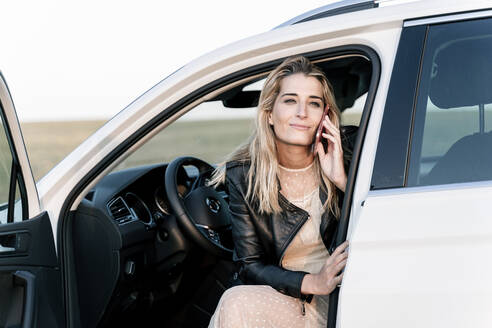 Blond woman using smartphone, sitting in white car - ERRF01522