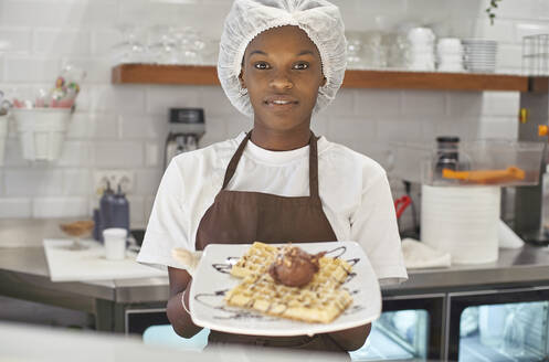 Young woman working in ice cream parlour, serving waffles with icecream - VEGF00382