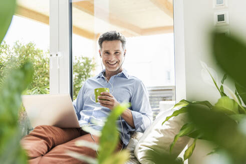 Mature man sitting on couch, using laptop, drinking coffee - UUF18105