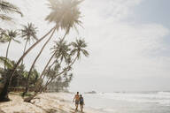 Rear view of romantic couple walking on sea shore at beach against sky, Sri Lanka - LHPF00719