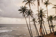 Woman looking at sea while standing by palm trees against cloudy sky, Sri Lanka - LHPF00722