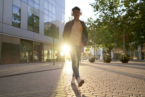 Portrait of smiling young man with headphones walking on street at backlight - DVGF00019