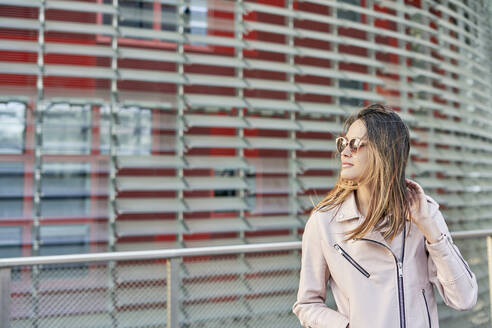 Portrait of woman wearing pink leather jacket and sunglasses, Barcelona, Spain - DVGF00022
