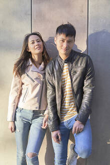 Portrait of couple wearing leather jackets leaning against wall - DVGF00028