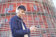Portrait of smiling young man with headphones looking at cell phone, Barcelona, Spain - DVGF00034