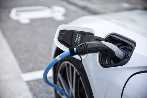 Electric car gettig charged at an charging station - MAMF00776