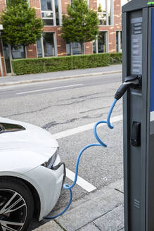Electric car gettig charged at an charging station - MAMF00779