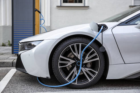 Electric car gettig charged at an charging station - MAMF00782