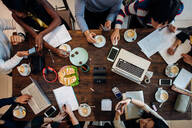 Female and male business team meeting at cafe table, overhead view - CUF52000