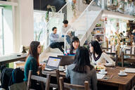 Young businesswomen remote working having meeting at cafe table - CUF52066
