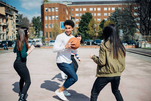Young female and male adult friends playing basketball on city court - CUF52069