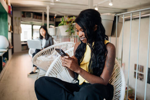 Young businesswoman looking at smartphone in cafe - CUF52102