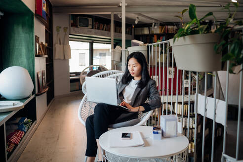 Young businesswoman using laptop in bookshop - CUF52105