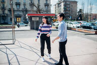 Young man and woman on city basketball court - CUF52117