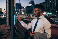 Businessman using digital information system at bus stop, Milano, Lombardia, Italy - CUF52192