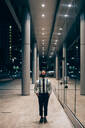 Businessman walking past mirrored wall of office building, Milano, Lombardia, Italy - CUF52201