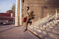 Businessman jumping off stairs of office building, Milano, Lombardia, Italy - CUF52228
