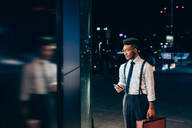 Businessman looking into window of shop - CUF52243