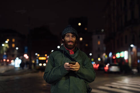 Bearded young man using smartphone on street - CUF52336