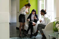 Three female business creatives taking a break and looking at smartphone in office - CUF52348
