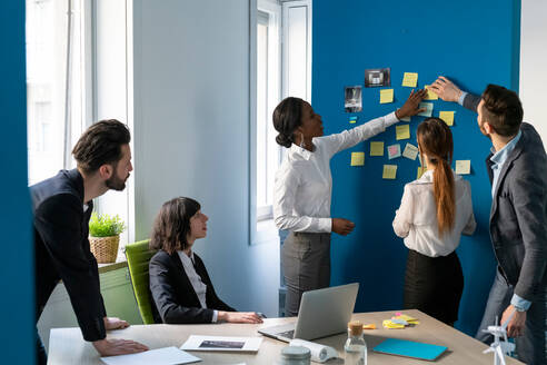 Young male and female business creative team having brainstorming office meeting with sticky notes - CUF52357