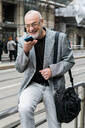 Businessman talking into smartphone on pavement, Milan, Lombardia, Italy - CUF52381