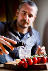 Man drinking wine and eating mediterranean food in cafe - CUF52387